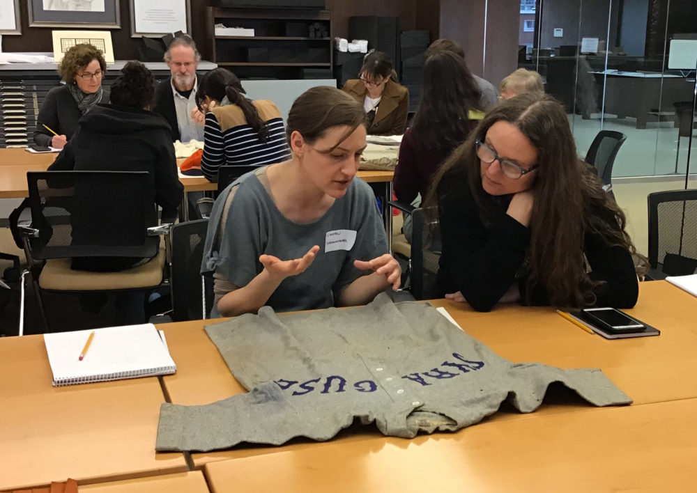 Two workshop participants examining a gray Syracuse University baseball uniform with Syracuse written on it in dark blue.