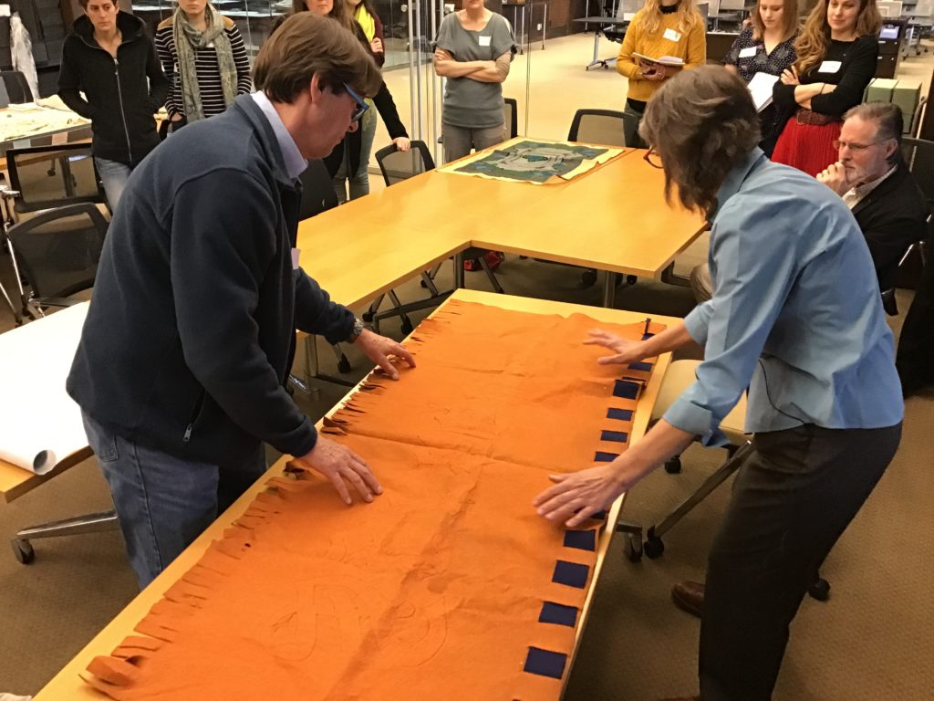 Conservator David Stokoe and Deborah Lee Trupin prepare an orange and blue banner for rolling by laying it out on a table..
