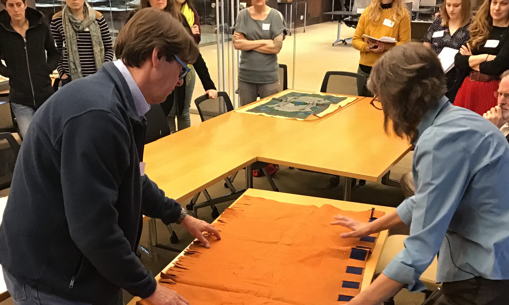 Conservator David Stokoe and guest speaker Deborah Trupin smooth out an orange and blue banner lying on a table.