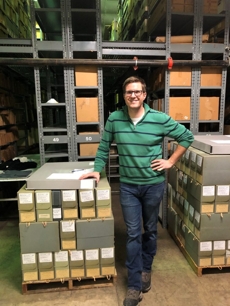 Dane Flansburgh standing next to archival boxes in a warehouse.