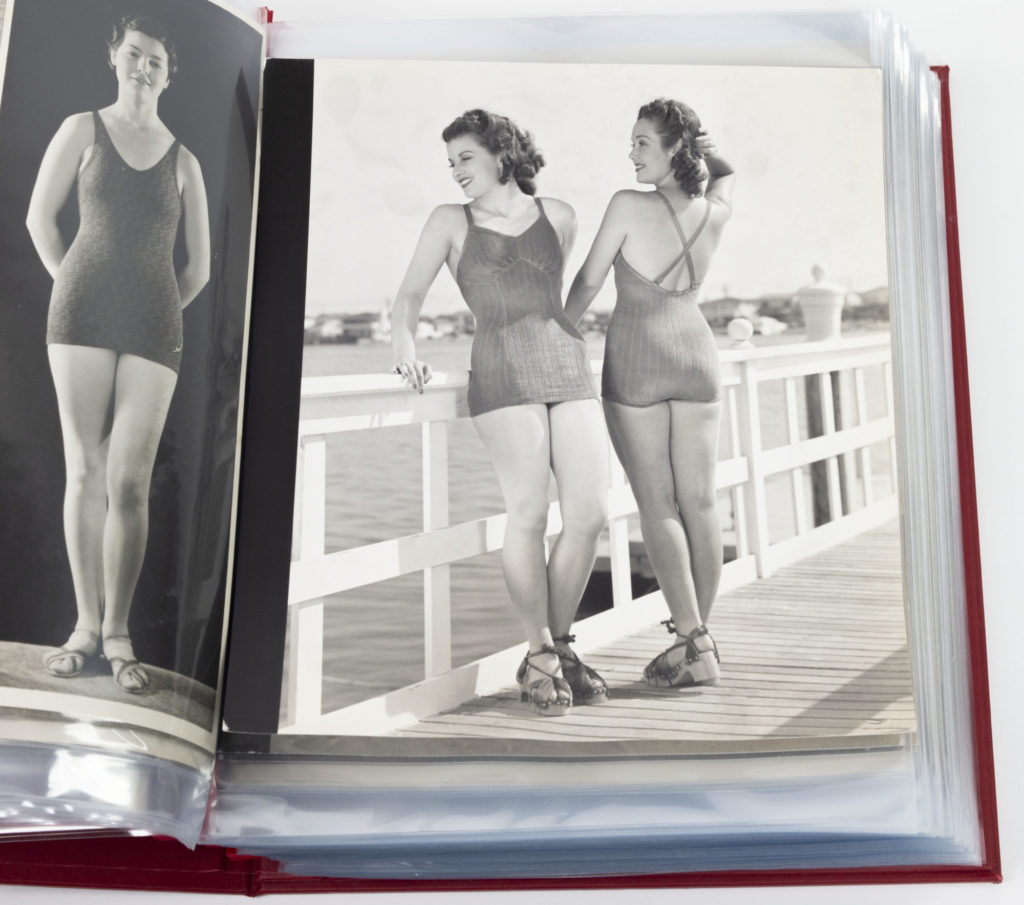 Models wearing swimsuits leaning on a railing