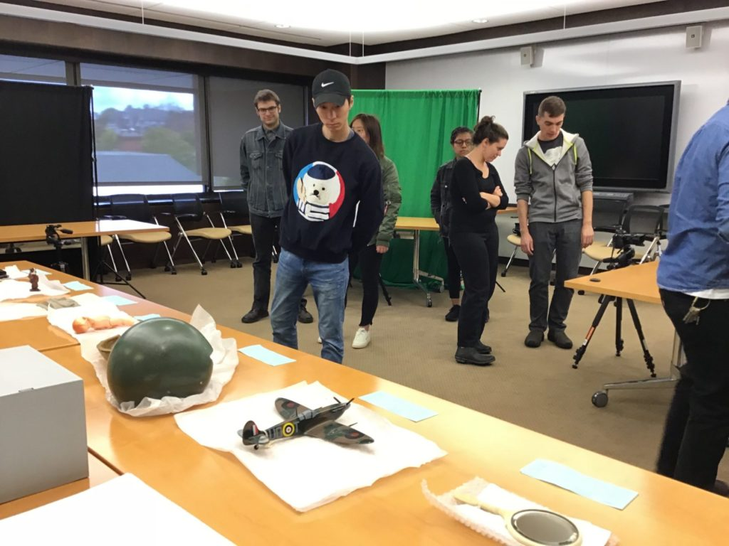 Students standing in classroom with artifacts displayed on tables