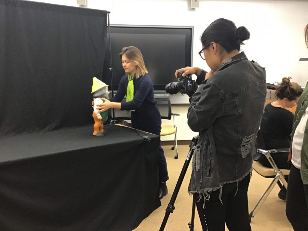 Plastics curator helping student photograph plastic object