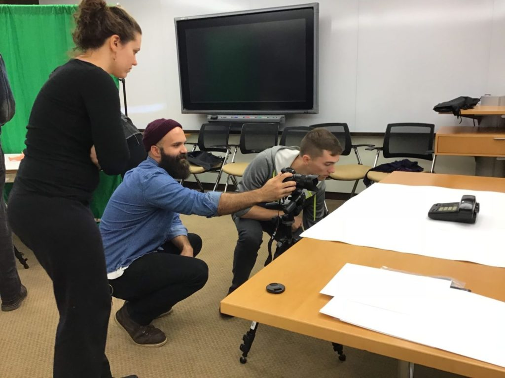 Teacher adjusting position of camera for student