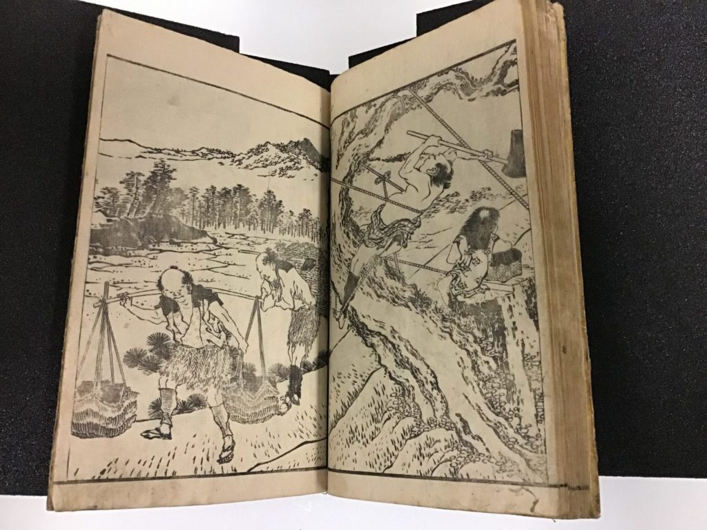 Image of a book opening with a woodblock image that takes up both pages and has a man walking through a landscape with a pole over his shoulders that supports two hanging basekets