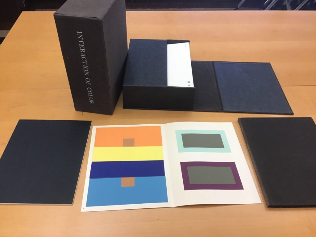 Paper with orange, yellow, dark blue, light blue, gray, and purple squares of paper attached inside, surrounded by black boxes and books on a wood table
