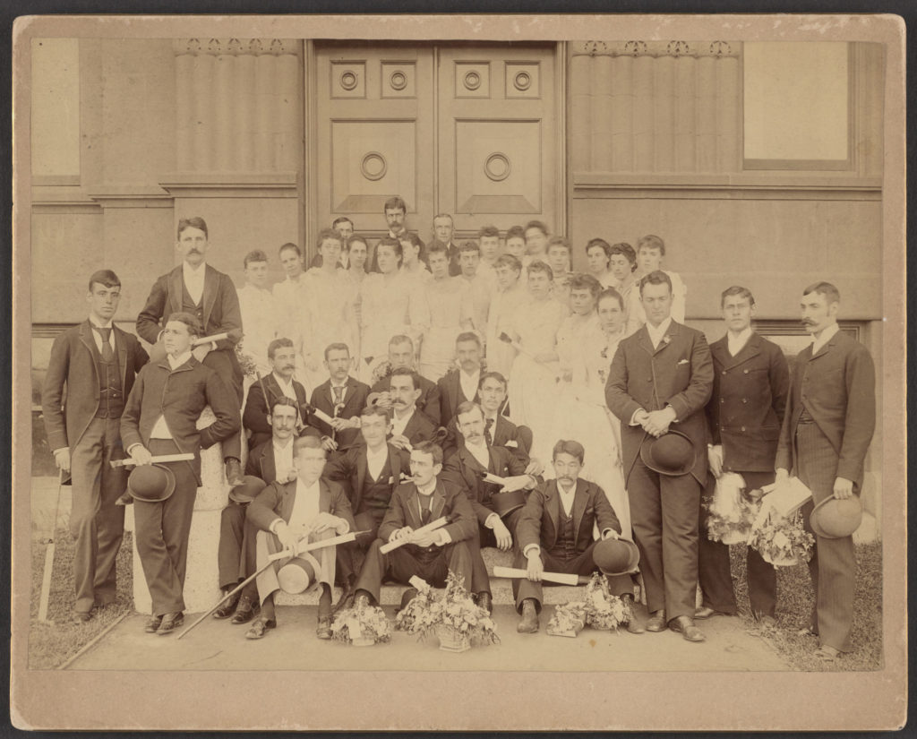 Group photo of men in suits and women in white dresses