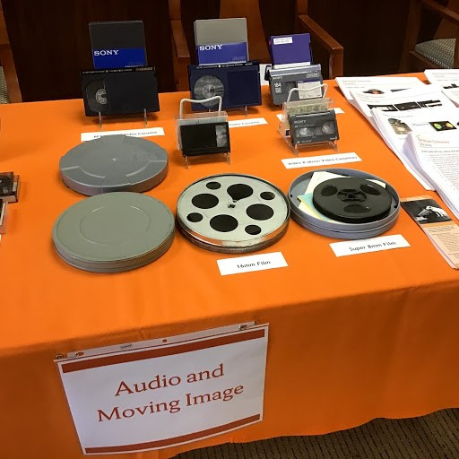 Film reels and VHS tapes on top of an orange covering of a table.
