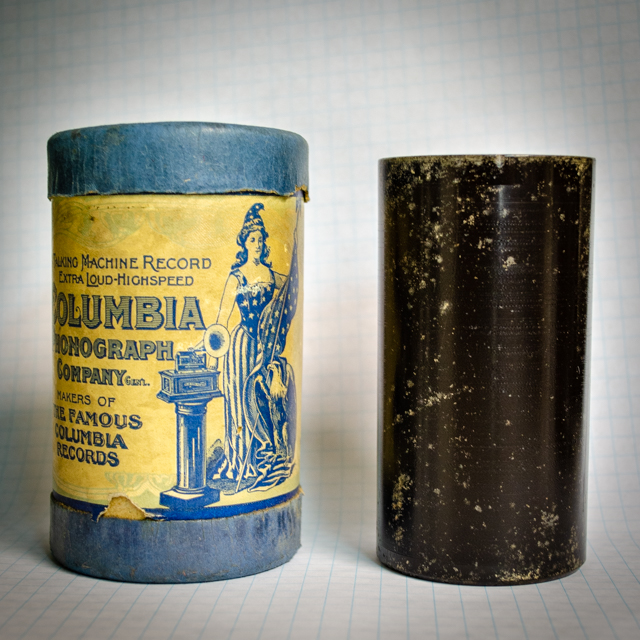 One blue and yellow and one black wax cylinder on top of graph paper.