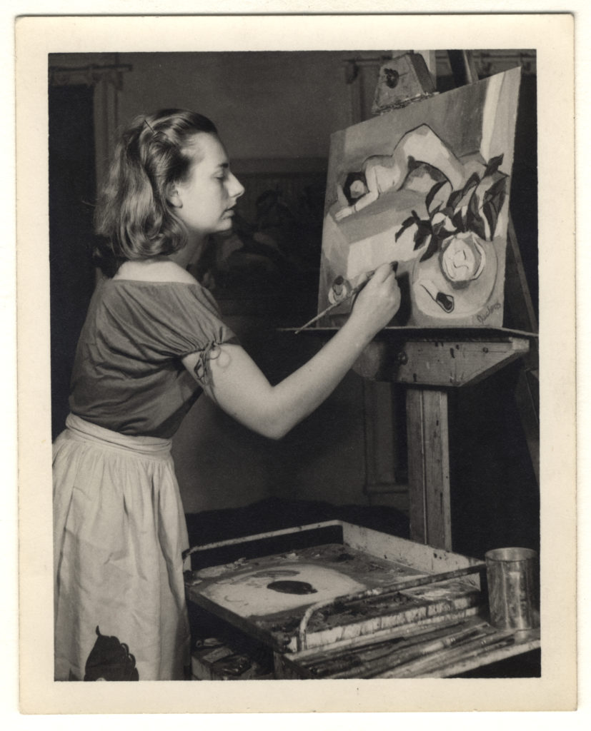 A woman painting a figural scene on canvas placed on an easel.