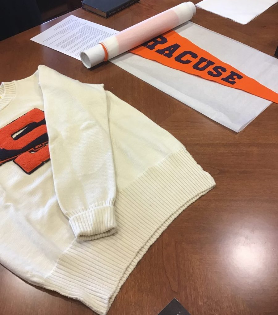 "A white sweatshirt with an embroidered orange letter 'S' and an orange textile stating ""Syracuse"" on top of a brown table."