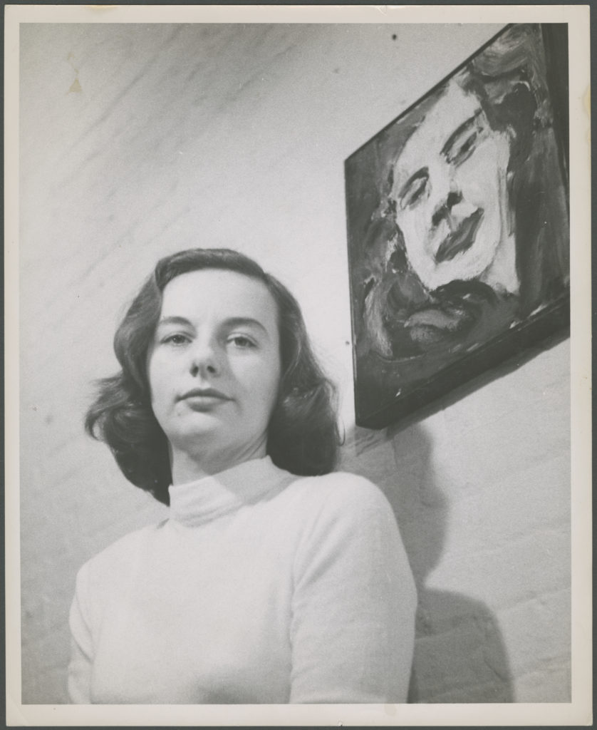 Black and white portrait photograph of a woman in a white sweater in front of a wall with a painting of her self-portrait.