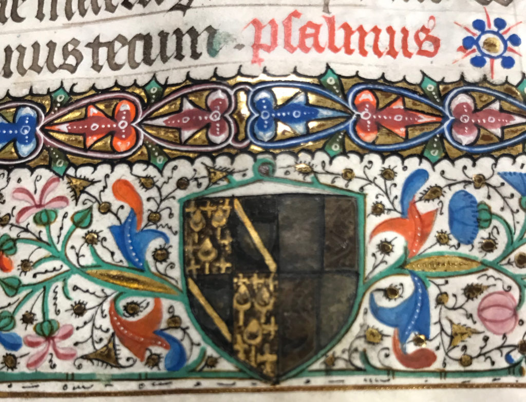 Close-up detail of a black and gold family crest with red, orange, pink, green, blue, and gold floral designs below red and black Latin text on vellum.