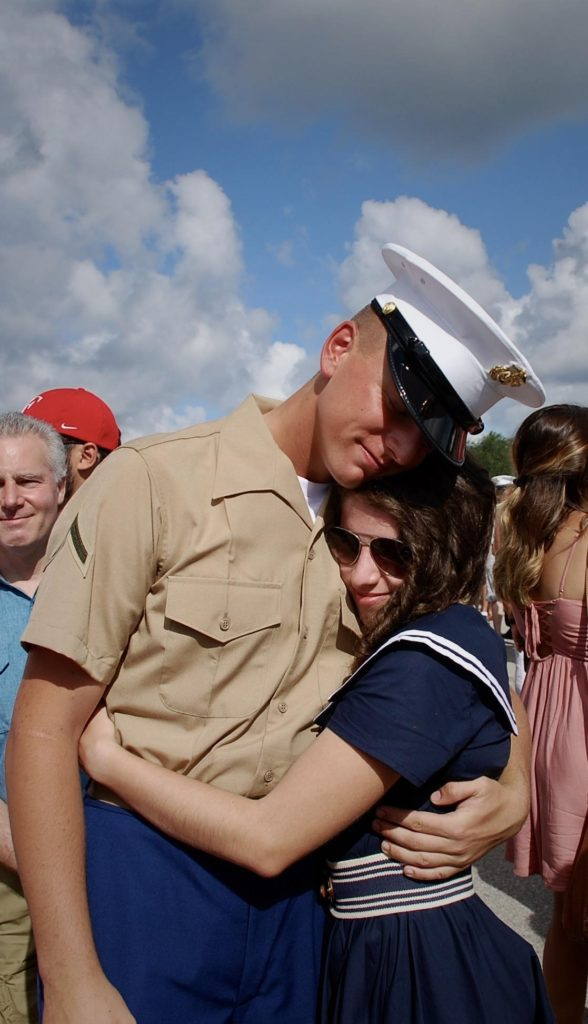 Man in uniform and a woman hugging with a crowd of people behind them.