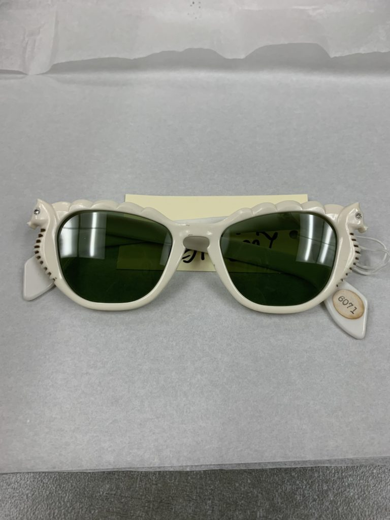 Pair of white sunglasses with seahorses on the sides of the lenses.