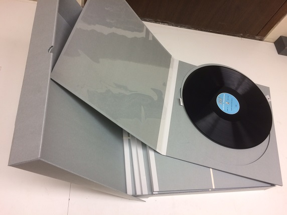 Multiple blue record sleeves with one opened blue sleeve on top and a black LP record inside.