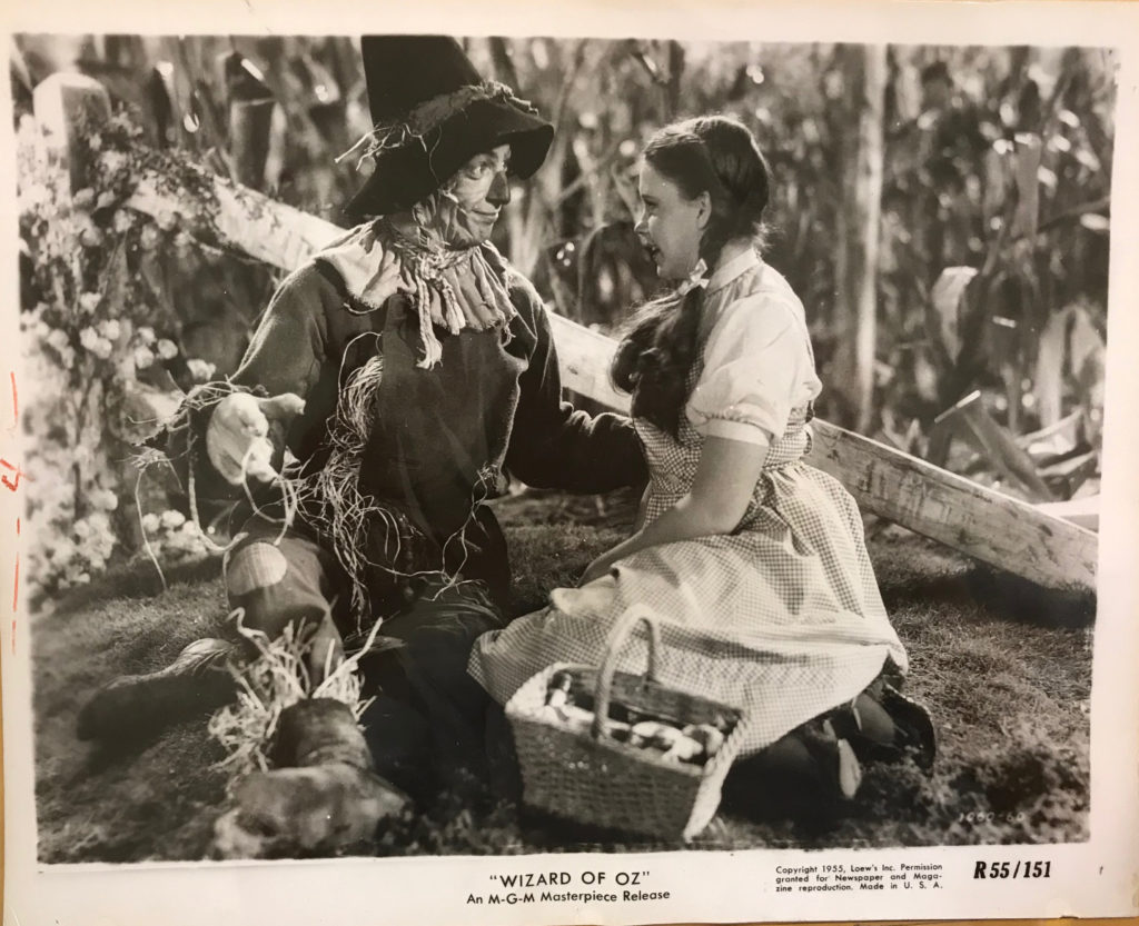 Black and white still from The Wizard of Oz depicting actors Judy Garland and Ray Bolger kneeling on the ground and looking at each other.