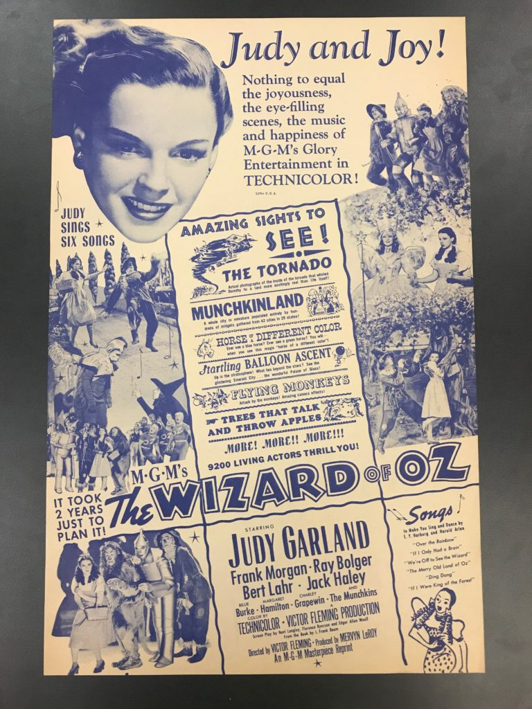 Blue and white poster advertising The Wizard of Oz film and picturing Judy Garland and multiple photographs depicting scenes from the movie.