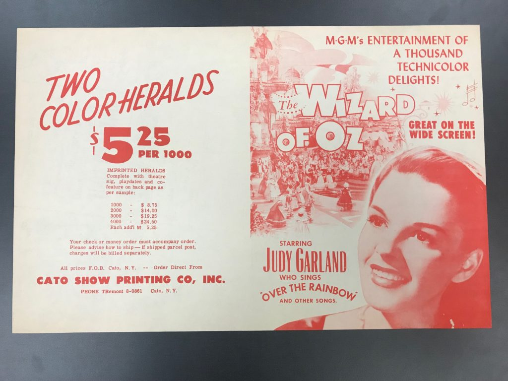 2. White and red poster advertising The Wizard of Oz film and picturing Judy Garland.