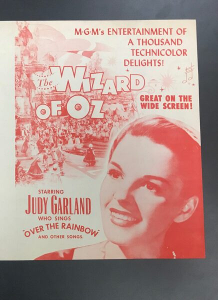 White and red poster advertising The Wizard of Oz film and picturing Judy Garland.
