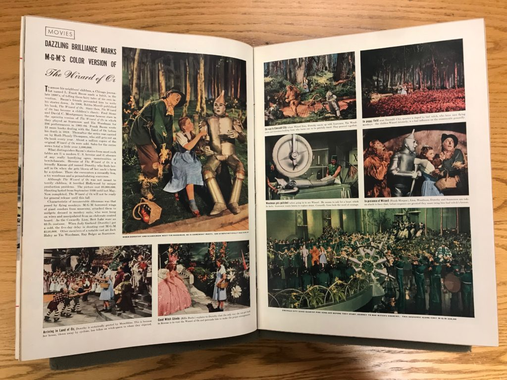 "An opened magazine with an ""Oz"" spread including text and colored images from the film."