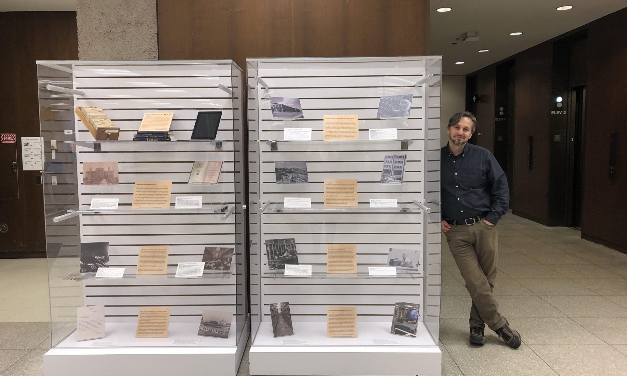 Sebastian Modrow standing next to exhibit cases