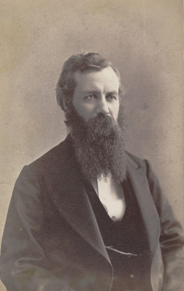 Portrait of Chancellor Winchell, a person in a dark suit and long beard.