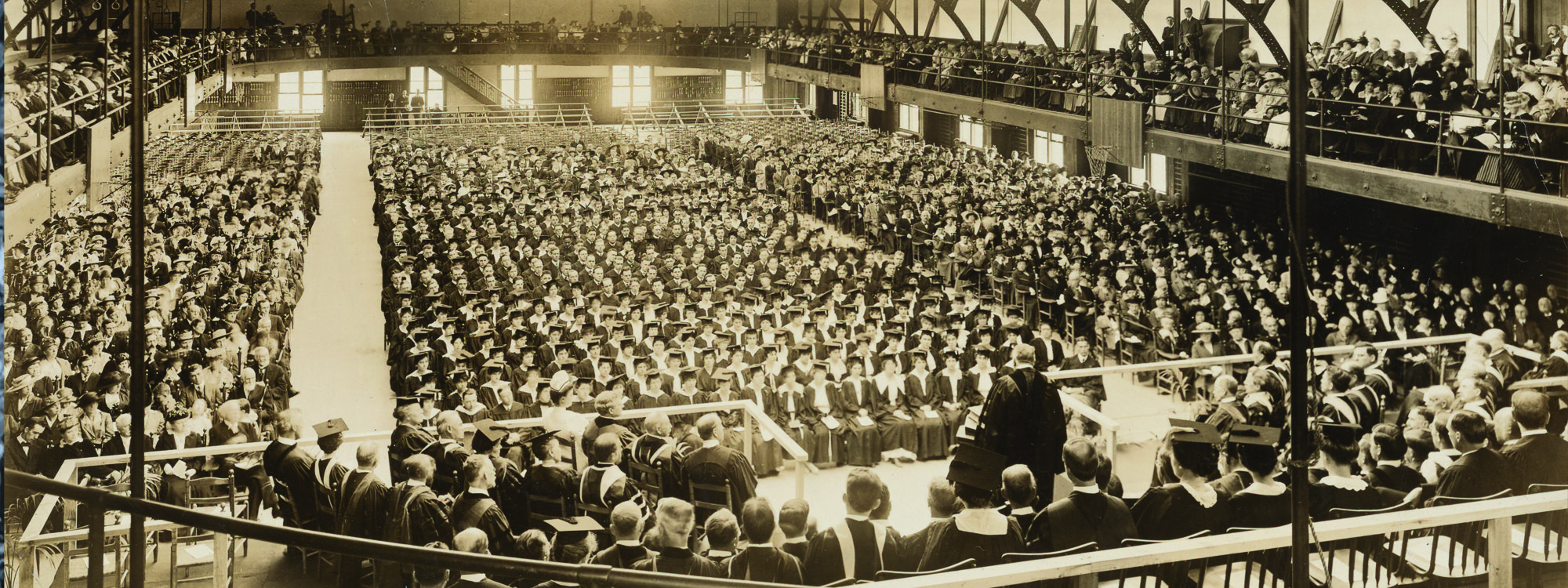 A speaker in academic regalia addresses the crowd of graduates in their caps and gowns in Archbold Gymnasium.