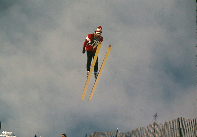 A skier wearing number 79 mid-air on the ski jump on South Campus