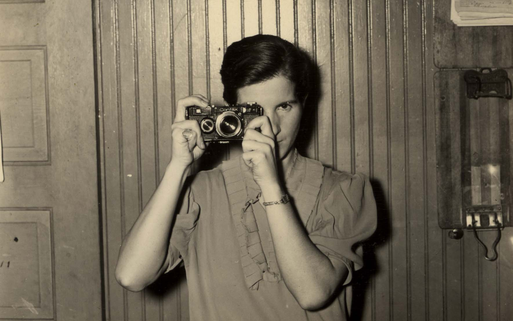 Woman holding camera in front of her right eye.