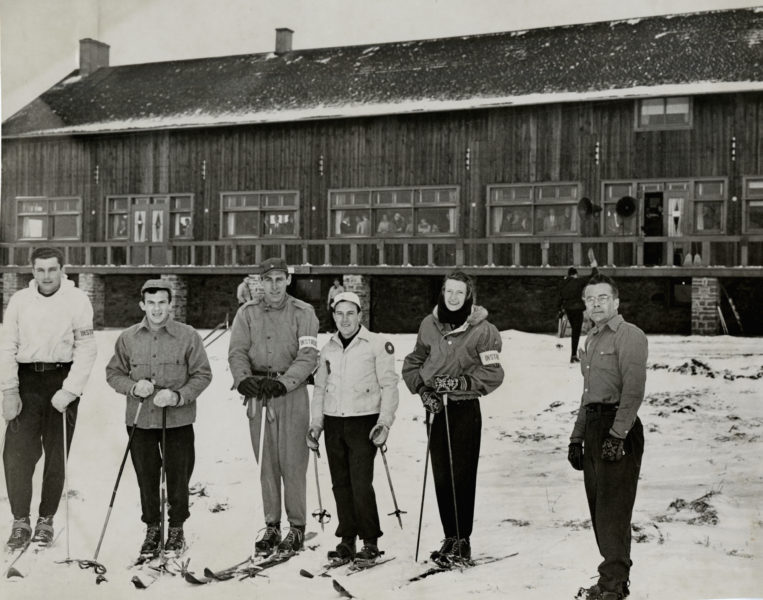 Group of skiers and ski coach gathered outside ski lodge