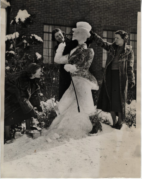 Three students working on a snow sculpture