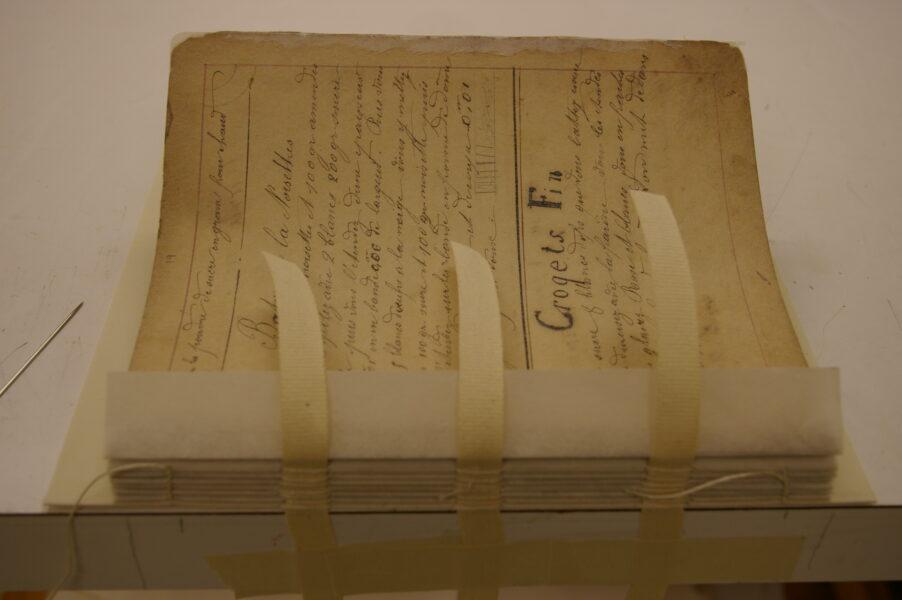 Repaired binding of 1800s cookbook.