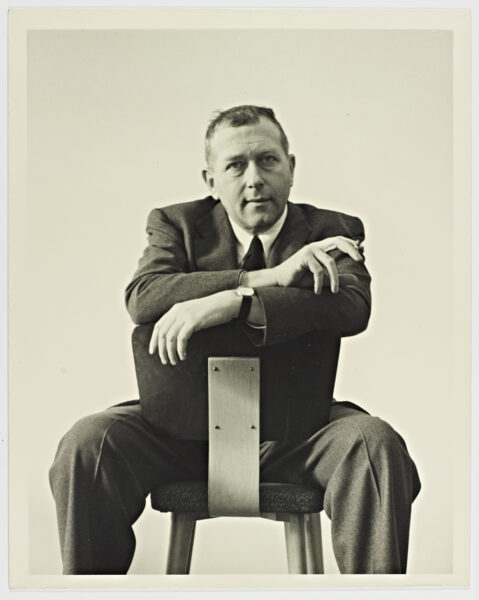 A black and white photograph of Marcel Breuer, sitting in a backwards chair with his arms crossed.