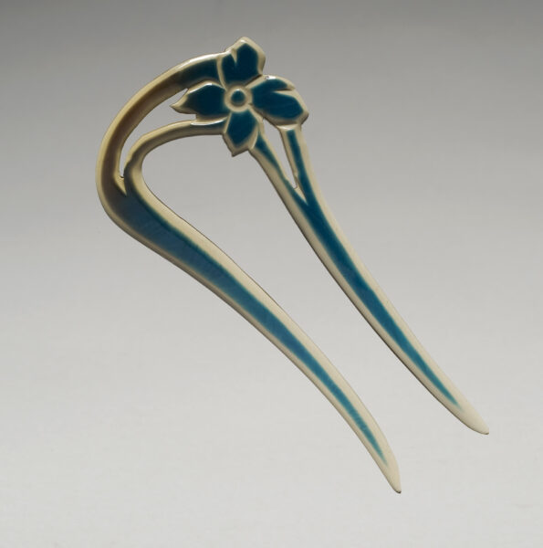 Blue two toothed hair pin with carved flower at top