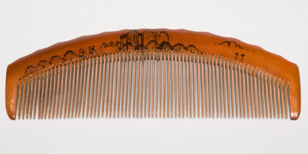 "Brown wooden comb with an etched image of a landscape and Chinese characters. Stamped ""140"" and ""Made in China"""