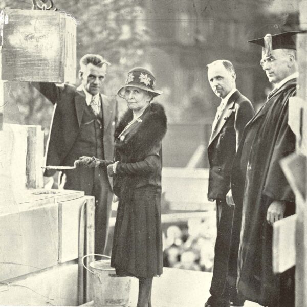 A woman and three men laying the cornerstone of Hendricks Chapel, three of whom are looking at the photographer.