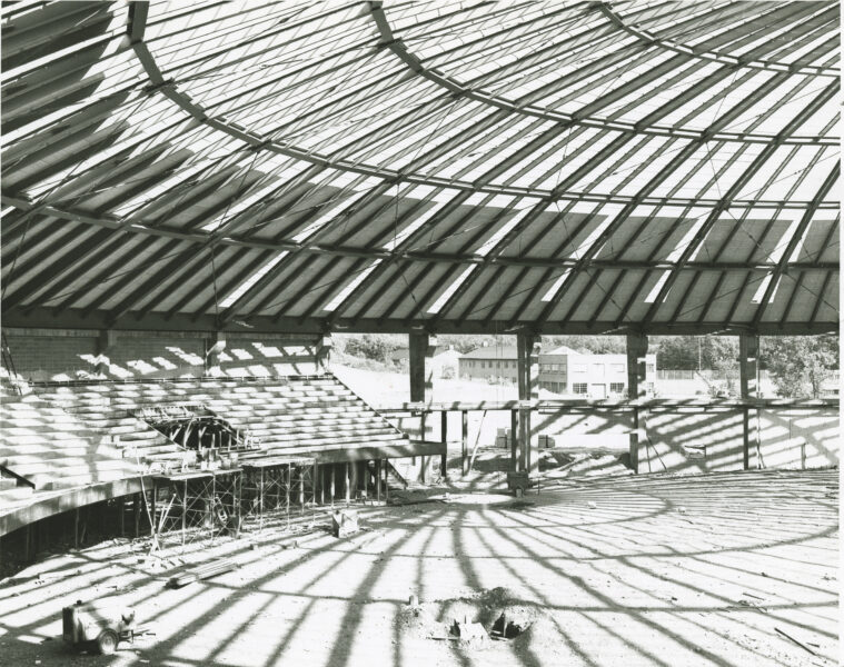 Interior view of Manley Field House under construction with light streaming in through the roof.