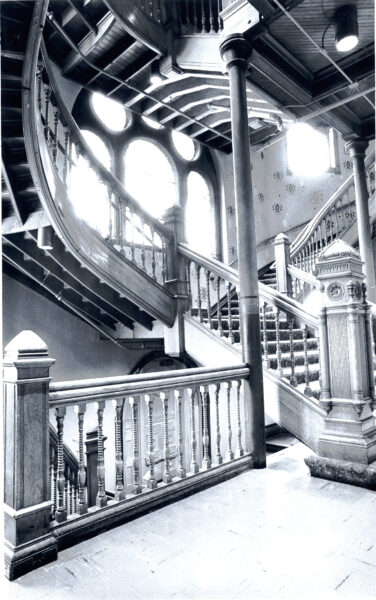 Interior view of the grand stairway in Crouse College with light streaming in through windows.