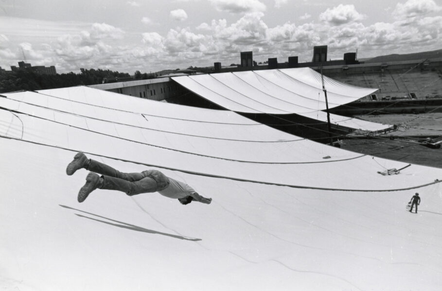 Man in midair about to slide down the uninflated roof of the Carrier Dome.