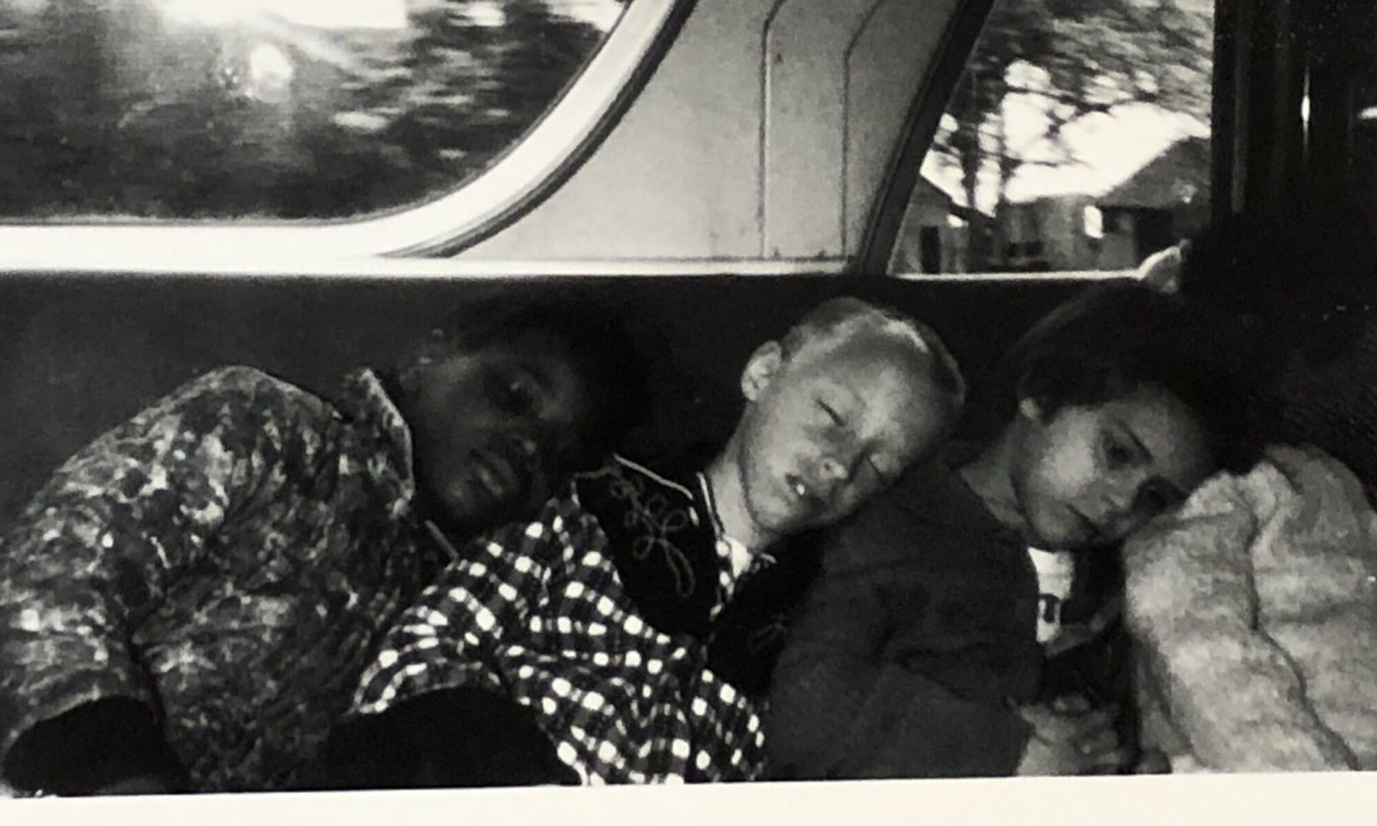 Four children, two white and two Black, lean on each on a bus bench. Three of the four children are sleeping