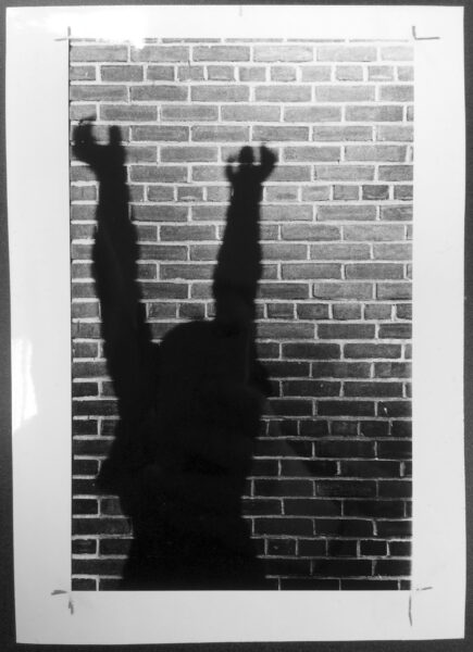 Shadow of statue Supplicant Persephone, featuring a woman reaching both hands upwards, on a brick wall.