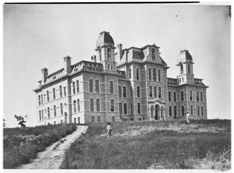 Exterior view of Hall of Languages with two men standing on lawn in front