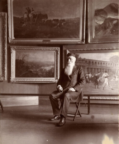 Black and white photograph of an older white man with a long white beard wearing a suit coat, trousers, and a black hat seated in front of a wall of landscape and architectural paintings