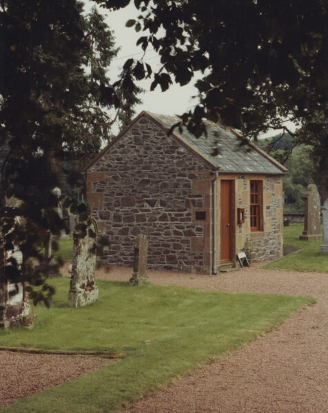 Small stone building in a grassy lawn.