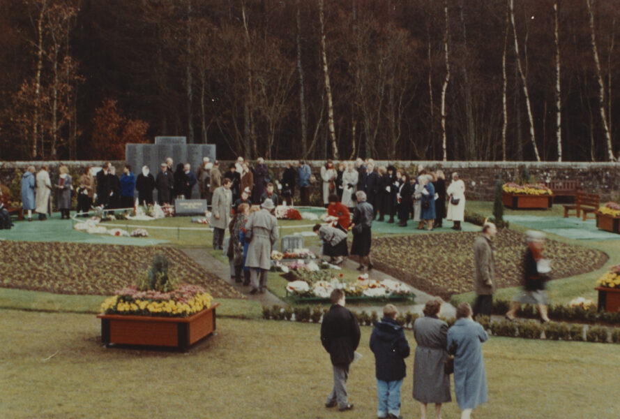 People gathered in garden near stone wall and flower beds.