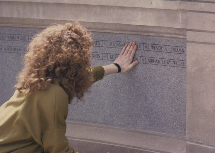A person with long, curly hair running their hand over names engraved on a stone wall.