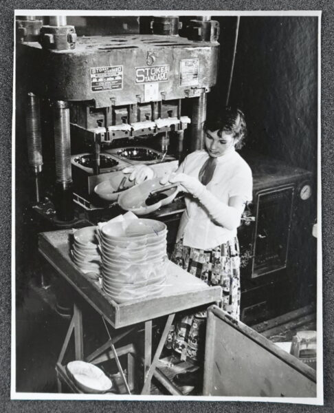 Female worker creating dishes in factory.