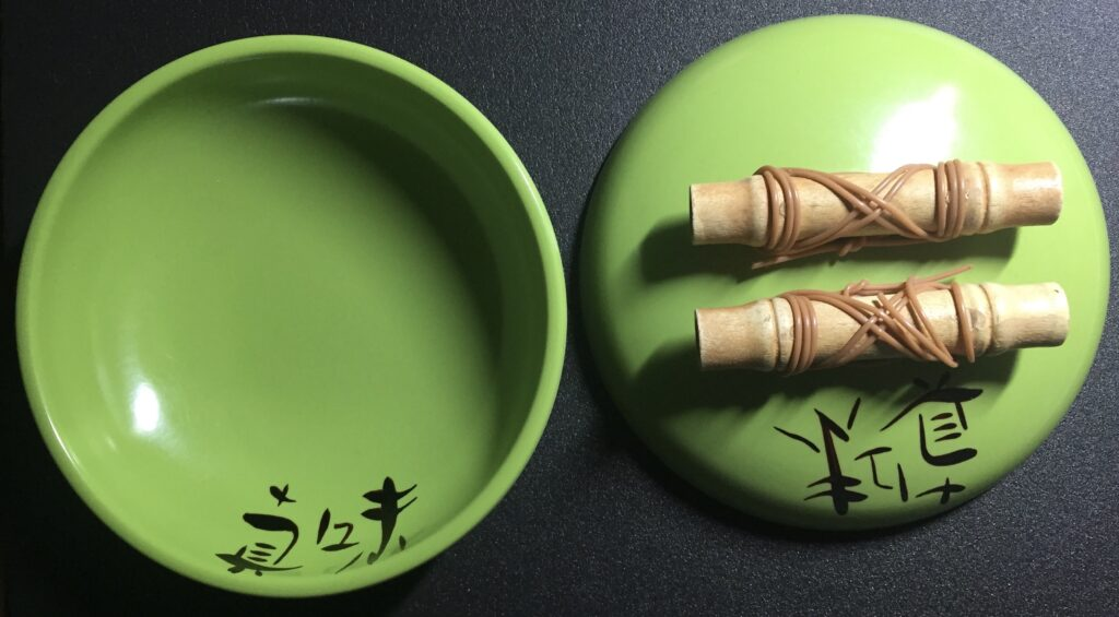 Green bowl and lid with bamboo handles.