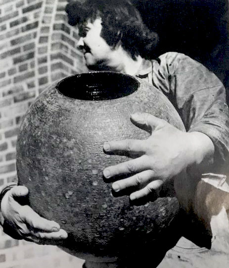 Black and white image of a woman, Maija Grotell, holding a large, round vase, 1941